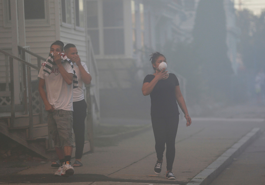 . People cover their faces to protect themselves from heavy smoke from a fire on Bowdoin Street in Lawrence, Mass., Thursday, Sept. 13, 2018. The company that owns Columbia Gas says its crews are performing safety checks after a series of fires and explosions erupted in three communities north of Boston. (Jessica Rinaldi/The Boston Globe via AP)