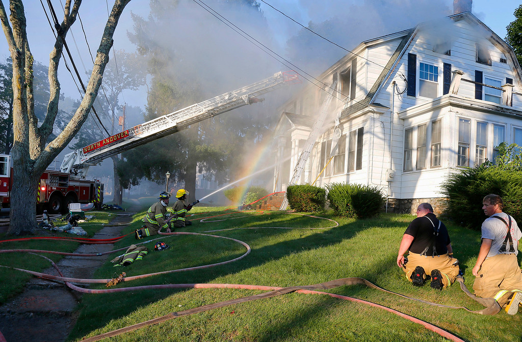 . Firefighters battle a house fire, Thursday, Sept. 13, 2018, on Herrick Road in North Andover, Mass., one of multiple emergency crews responding to a series of gas explosions and fires triggered by a problem with a gas line that feeds homes in several communities north of Boston. (AP Photo/Mary Schwalm)