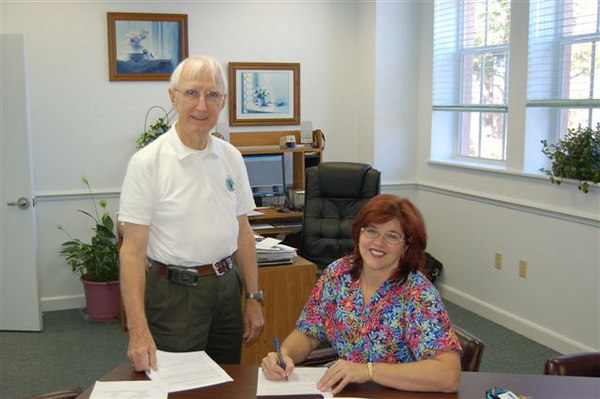 Kenneth Smith watches as Belleview Mayor Tammy C. Moore signs the Gateway Community Proclamation.