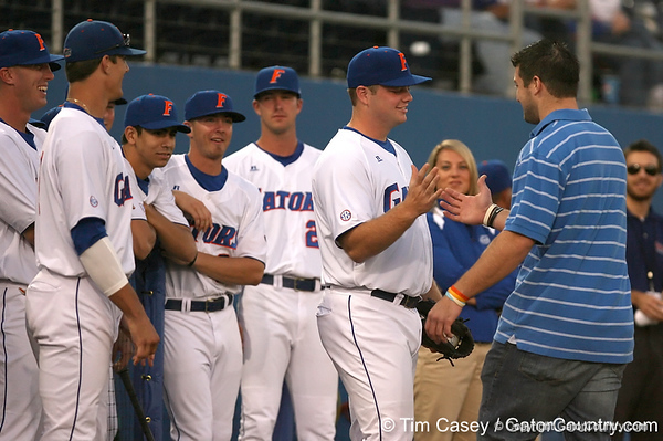 photo by Tim Casey<br /> <br /> Florida senior catcher Teddy Foster greets senior quarterback Tim Tebow after he threw out the first pitch during the Gators' 8-5 loss to the Miami Hurricanes on Friday, February 27, 2009 at McKethan Stadium in Gainesville, Fla.