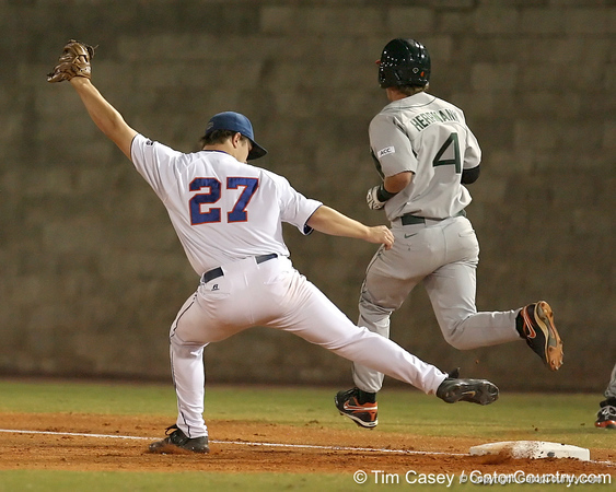 photo by Tim Casey<br /> <br /> Florida senior pitcher Patrick Keating is late covering first base as Chris Herrmann is safe during the Gators' 8-5 loss to the Miami Hurricanes on Friday, February 27, 2009 at McKethan Stadium in Gainesville, Fla.