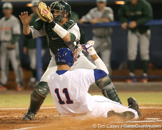 photo by Tim Casey<br /> <br /> Florida sophomore outfielder Riley Cooper slides past Yasmani Grandal on a sacrifice fly by Matt den Dekker during the third inning of the Gators' 8-5 loss to the Miami Hurricanes on Friday, February 27, 2009 at McKethan Stadium in Gainesville, Fla.