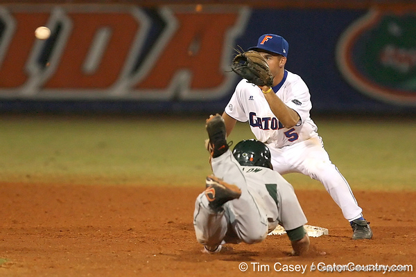 photo by Tim Casey<br /> <br /> Florida junior shortstop Mike Mooney attempts to catch Dave DiNatale stealing on a play that was negated by a walk during the eighth inning of the Gators' 8-5 loss to the Miami Hurricanes on Friday, February 27, 2009 at McKethan Stadium in Gainesville, Fla.