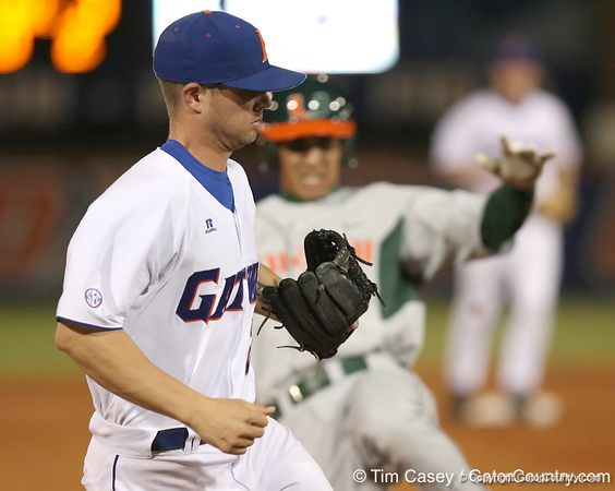 photo by Tim Casey<br /> <br /> Florida sophomore Josh Adams steps on third base ahead of Harold Martinez for the final out of the Gators' 8-5 loss to the Miami Hurricanes on Friday, February 27, 2009 at McKethan Stadium in Gainesville, Fla.
