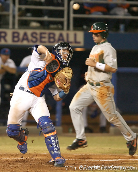 photo by Tim Casey<br /> <br /> Florida junior catcher Buddy Munroe turns a double play by throwing to first base during the eighth inning of the Gators' 8-5 loss to the Miami Hurricanes on Friday, February 27, 2009 at McKethan Stadium in Gainesville, Fla.
