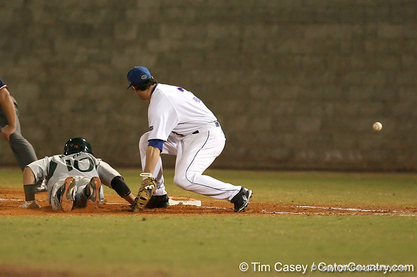 photo by Tim Casey<br /> <br /> Florida senior first baseman Brandon McArthur misses an errant throw by Patrick Keating during the third inning of the Gators' 8-5 loss to the Miami Hurricanes on Friday, February 27, 2009 at McKethan Stadium in Gainesville, Fla.