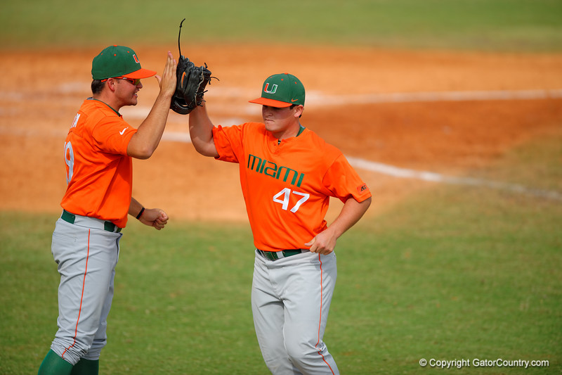 Miami Hurricanes pitcher Enrique Sosa is high fived by teammate Bryan Garcia after Sosa got out of a jam in the fifth inning.  Florida Gators vs Miami Hurricanes.  February 22nd, 2015. Gator Country photo by David Bowie.
