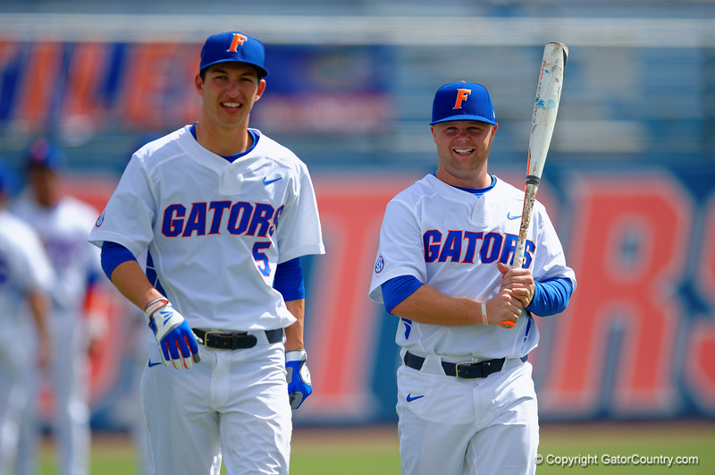 Florida Gators infielder Dalton Guthrie and Florida Gators OF/LHP Logan Browning walk toward the dugout smiling and laughing during pre-game.   Florida Gators vs Miami Hurricanes.  February 22nd, 2015. Gator Country photo by David Bowie.