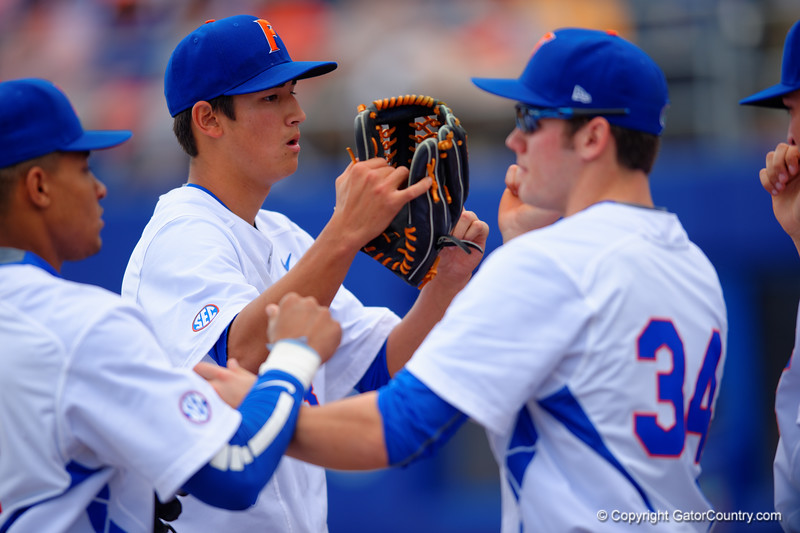 Florida Gators pitcher Dane Dunning getting high fives after ending the first inning.  Florida Gators vs Miami Hurricanes.  February 22nd, 2015. Gator Country photo by David Bowie.