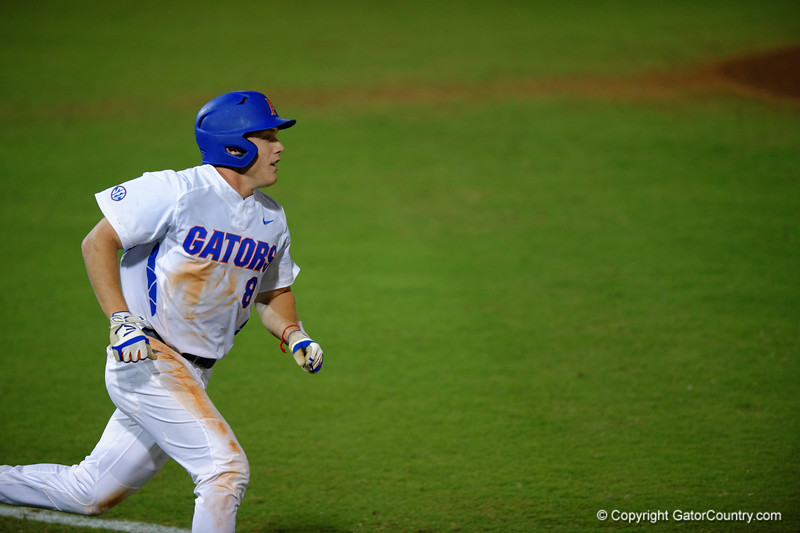 Florida Gators outfielder Harrison Bader swings and drives the a ball for a single in the fifth inning.  Florida Gators Baseball vs Florida State Seminoles.  March 17th, 2016. Gator Country photo by David Bowie.
