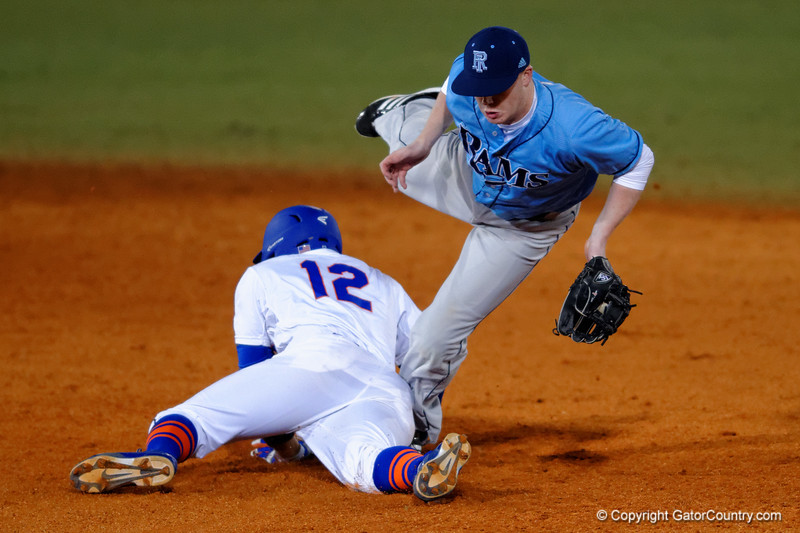 Florida Gators shortstop Richie Martin slides into second base knocking over the Rhode Island infielder.  Florida Gators vs Rhode Island Rays.  February 13th, 2015. Gator Country photo by David Bowie.