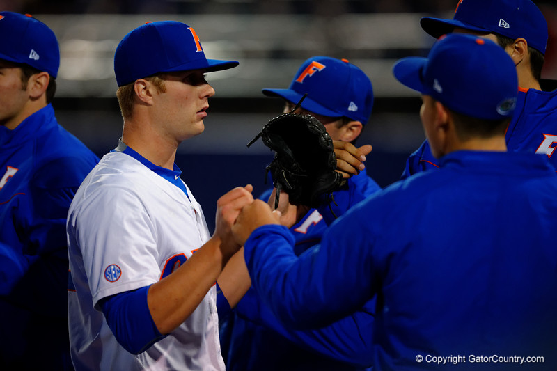 The Florida Gators congratulate pitcher Logan Shore after he ended the fourth inning.  Florida Gators vs Rhode Island Rays.  February 13th, 2015. Gator Country photo by David Bowie.