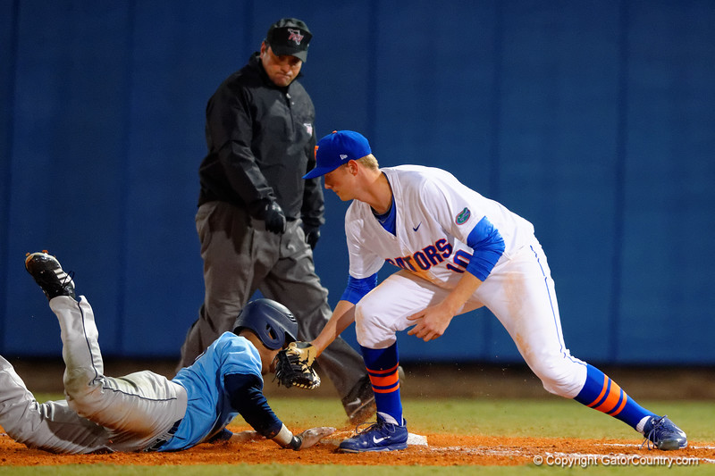 Florida Gators first baseman A.J. Puk attempts to pick off a Rhode Island baserunner.  Florida Gators vs Rhode Island Rays.  February 13th, 2015. Gator Country photo by David Bowie.