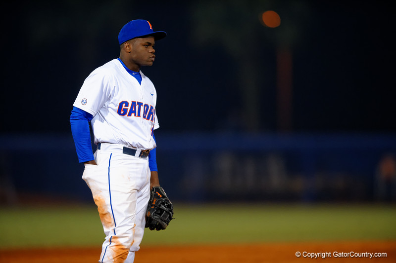 Florida Gators infielder Josh Tobias puts his hand in his back pocket to warm it up with the temperature dipping down into the 40s.  Florida Gators vs Rhode Island Rays.  February 13th, 2015. Gator Country photo by David Bowie.
