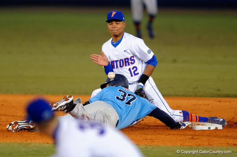 Rhode Island infielder Mike Corin is hit in the head while sliding back toward second base to avoid being tagged out.  Florida Gators vs Rhode Island Rays.  February 13th, 2015. Gator Country photo by David Bowie.