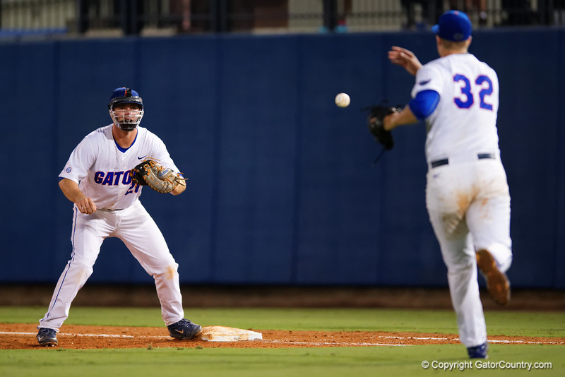Florida Gators pitcher Logan Shore underhands the ball to Florida Gators infielder Peter Alonso for a force out during Thursday nights Gators loss to the Auburn Tigers 4-1.  May 14th, 2015. Gator Country photo by David Bowie.