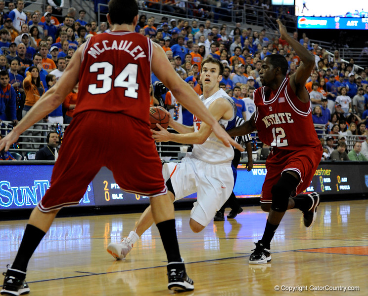 (Casey Brooke Lawson / Gator Country) UF forward Nick Calathes moves the ball past North Carolina State guard Farnold Degand and forward ben McCauley during the first half of the Gators game against the Wolfpack in Gainesville, Fla., on January 3, 2009. The Gators won 68 to 66.