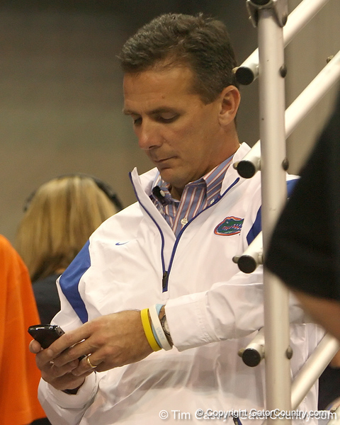 photo by Tim Casey<br /> <br /> Florida head football coach Urban Meyer looks at his phone during first half of the Gators' 80-65 win against the Arkansas Razorbacks on Saturday, January 17, 2009 at the Stephen C. O'Connell Center in Gainesville, Fla.