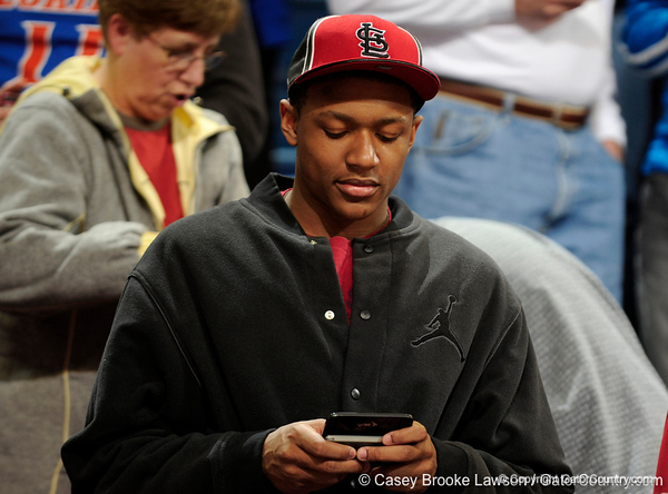 A University of Florida basketball recruit glances at his cell phone during the Gators 64-76 loss to the Musketeers in Gainesville, Fla., on Saturday, February 13, 2010. / Gator Country photo by Casey Brooke Lawson