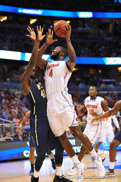 Florida center Patric Young leaps over Pitt center Talib Zanna and lays in the basket.  Florida Gators vs Pitt Panthers.  March 22nd, 2014.  Gator Country photo by David Bowie.