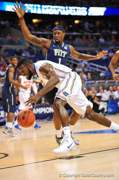 Florida center Patric Young dribbles past Pitt forward Jamel Artis.  Florida Gators vs Pitt Panthers.  March 22nd, 2014.  Gator Country photo by David Bowie.