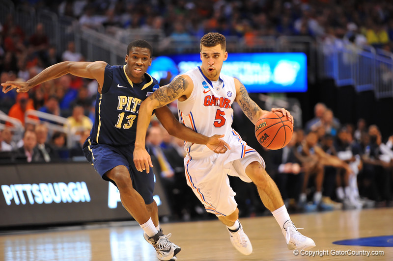 Florida guard Scottie Wilbekin dribbles up court and past Pitt guard Josh Newkirk.  Florida Gators vs Pitt Panthers.  March 22nd, 2014.  Gator Country photo by David Bowie.