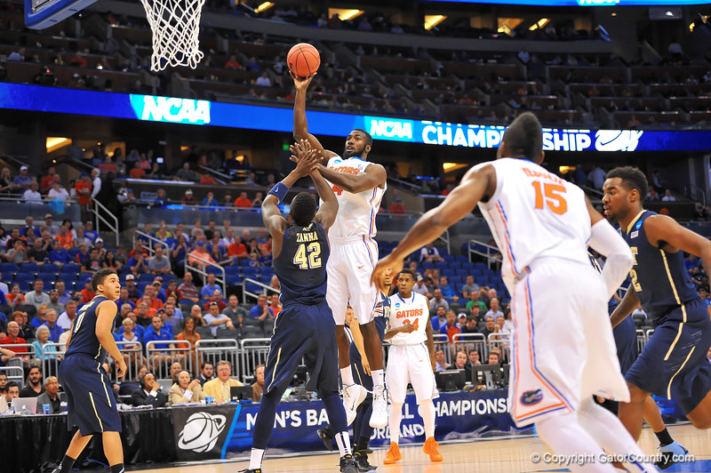 Florida center Patric Young turns and shoots over Pitt center Talib Zannain the first half.  Florida Gators vs Pitt Panthers.  March 22nd, 2014.  Gator Country photo by David Bowie.