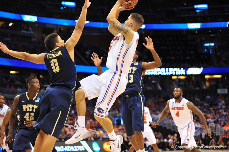 Florida guard Scottie Wilbekin leaps for the jump shot over the arm of Pitt guard James Robinson.  Florida Gators vs Pitt Panthers.  March 22nd, 2014.  Gator Country photo by David Bowie.