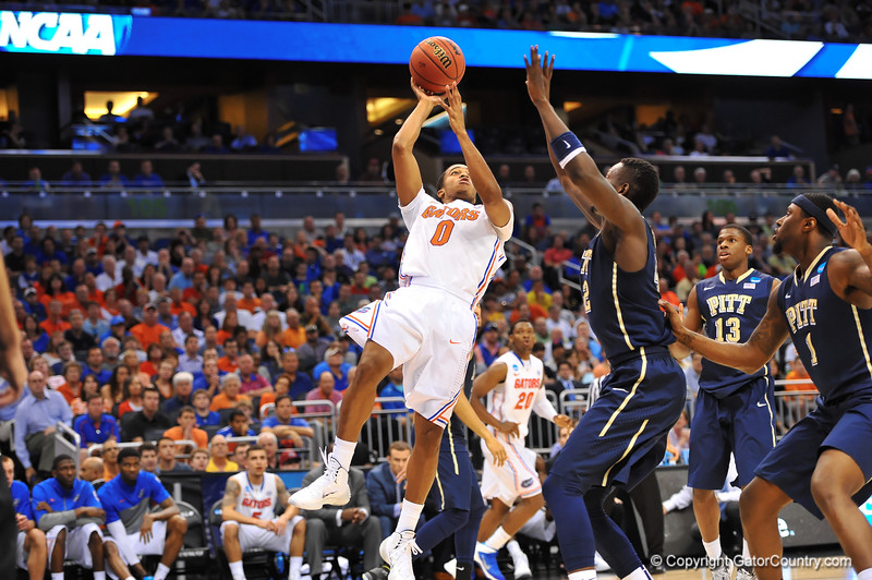 Florida guard Kasey Hill drives to the net and puts up the shot over Pitt center Talib Zanna.  Florida Gators vs Pitt Panthers.  March 22nd, 2014.  Gator Country photo by David Bowie.