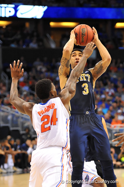 Pitt guard Cameron Wright leaps up for the shot attempt over Florida forward Casey Prather.  Florida Gators vs Pitt Panthers.  March 22nd, 2014.  Gator Country photo by David Bowie.