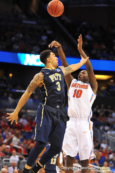 Florida forward Dorian Finney-Smith drains a 3-pointer in the second half over Pitt guard Cameron Wright.  Florida Gators vs Pitt Panthers.  March 22nd, 2014.  Gator Country photo by David Bowie.