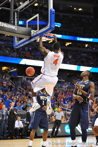Florida center Patric Young hangs onto the rim after a monster dunk in the second half.  Florida Gators vs Pitt Panthers.  March 22nd, 2014.  Gator Country photo by David Bowie.
