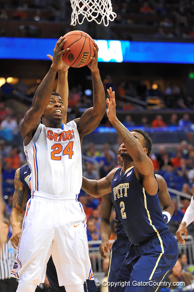 Florida forward Casey Prather leaps up and attempts the reverse layin over Pitt forward Michael Young.  Florida Gators vs Pitt Panthers.  March 22nd, 2014.  Gator Country photo by David Bowie.