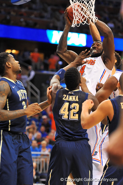 Florida center Patric Young leaps up for the offensive rebound over Pitt center Talib Zanna.  Florida Gators vs Pitt Panthers.  March 22nd, 2014.  Gator Country photo by David Bowie.