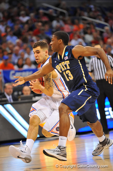 Florida guard Scottie Wilbekin drives to the net while being guarded by Pitt guard Josh Newkirk.  Florida Gators vs Pitt Panthers.  March 22nd, 2014.  Gator Country photo by David Bowie.