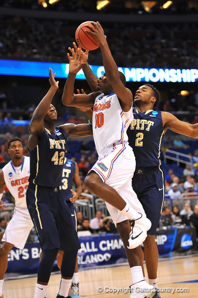 Florida forward Dorian Finney-Smith races toward the basket and past Pitt center Talib Zanna and Pitt forward Michael Young.  Florida Gators vs Pitt Panthers.  March 22nd, 2014.  Gator Country photo by David Bowie.
