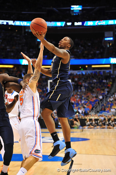 Pitt forward Lamar Patterson drives to the basket and lays in the shot over Florida guard Scottie Wilbekin.  Florida Gators vs Pitt Panthers.  March 22nd, 2014.  Gator Country photo by David Bowie.