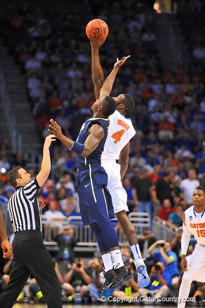 Florida center Patric Young leaps up and over against Pitt center Talib Zanna and swats the ball back to Florida forward Will Yeguete.  Florida Gators vs Pitt Panthers.  March 22nd, 2014.  Gator Country photo by David Bowie.