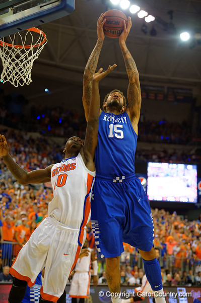 Kentucky Wildcats forward Willie Cauley-Stein leaps over Florida Gators forward Dorian Finney-Smith for a rebound during the first half.  Florida Gators vs Kentucky Wildcats.  February 7th, 2015. Gator Country photo by David Bowie.