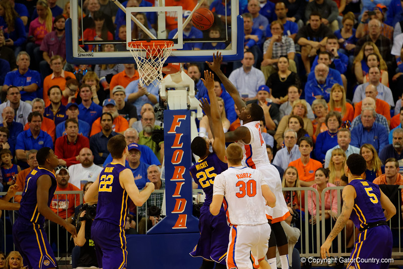 Florida Gators forward Dorian Finney-Smith leaps over LSU Tigers forward Jordan Mickey and scores during the second half.  Florida Gators vs LSU Tigers.  January 20th, 2015. Gator Country photo by David Bowie.