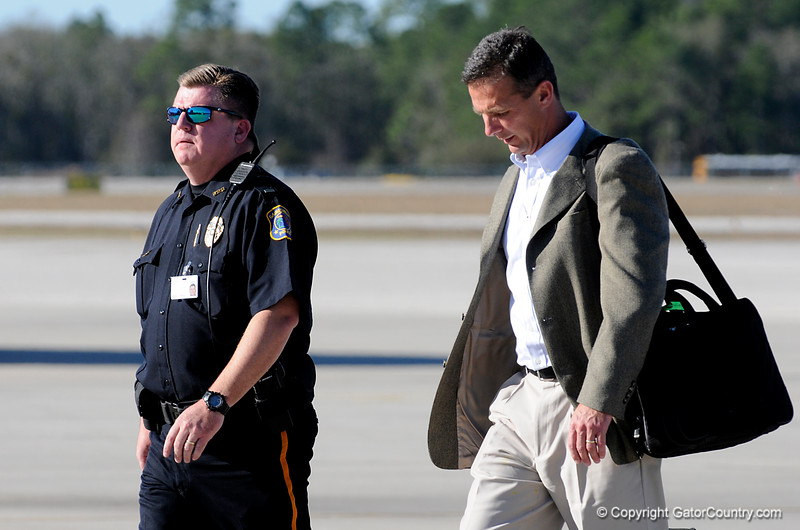 (Casey Brooke Lawson / Gator Country) UF Head Coach Urban Meyer  is escorted by a police officer at the Gainesville Regional Airport after his champion football team returns from Miami, after winning the 2008 National College Football Championship, in Gainesville, Fla., on January 9, 2009.