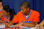A Florida Gator cheerleader signs a poster for a fan during the 2014 Florida Gator Fan Day.  August 16th, 2014. Gator Country photo by David Bowie.