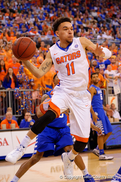 Florida Gators guard Chris Chiozza drives to the basket and passes the ball out from under the basket.  Florida Gators vs Kentucky Wildcats.  February 7th, 2015. Gator Country photo by David Bowie.