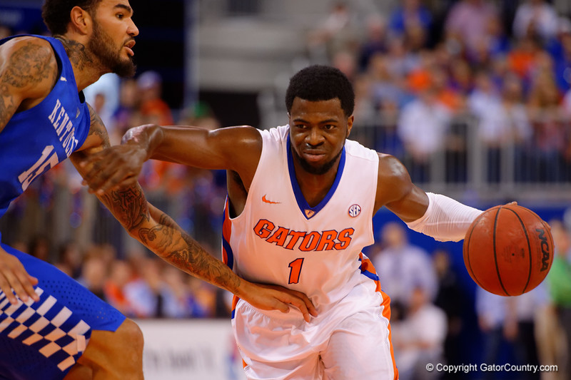 Florida Gators guard Eli Carter dribbles past Kentucky Wildcats forward Willie Cauley-Stein during the first half.  Florida Gators vs Kentucky Wildcats.  February 7th, 2015. Gator Country photo by David Bowie.