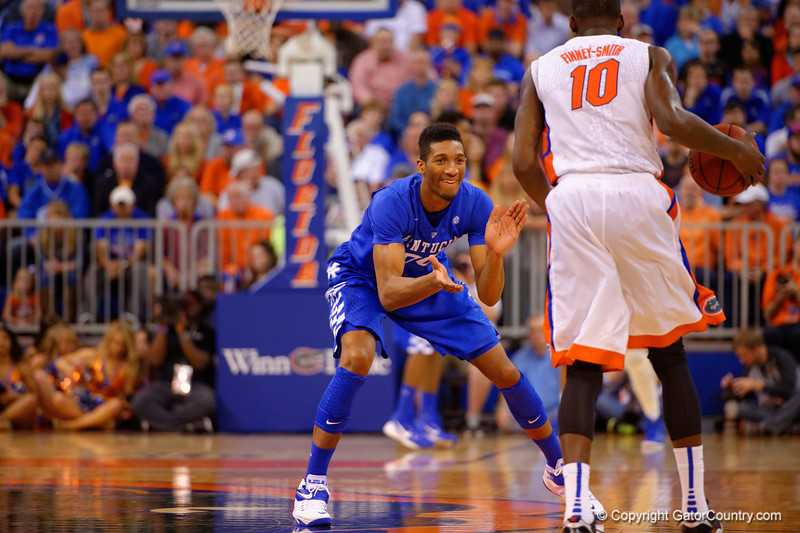Kentucky Wildcats forward Marcus Lee smiles and claps at Florida Gators forward Dorian Finney-Smith as he dribbles toward him.  Florida Gators vs Kentucky Wildcats.  February 7th, 2015. Gator Country photo by David Bowie.