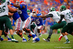 Florida Gators running back Brandon Powell tries to find the open hole before being tackled by Eastern Michigan defensive lineman Mike Steals.  Florida Gators vs Eastern Michigan Eagles.  September 6th, 2014. Gator Country photo by David Bowie.