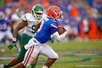 Florida Gators quarterback Treon Harris looks to throw downfield but tucks the ball and sprints downfield.  Florida Gators vs Eastern Michigan Eagles.  September 6th, 2014. Gator Country photo by David Bowie.
