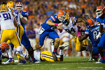 Florida Gators quarterback Jeff Driskel leaps over an LSU Tigers defender and downfield for a first down during the first half.  Florida Gators vs LSU Tigers.  October 11th, 2014. Gator Country photo by David Bowie.