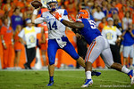 Kentucky Wildcats quarterback Patrick Towles, being rushed by Florida Gators defensive lineman Darious Cummings, throws the ball away leading to an intentional grounding call on their own 3 yard line late in the fourth quarter.  Florida Gators vs Kentucky Wildcats.  September 13th, 2014. Gator Country photo by David Bowie.