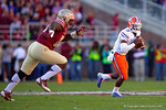 Florida Gators quarterback Treon Harris scrambles to avoid a FSU defender in the first quarter.  Florida Gators vs FSU Seminoles.  November 22th, 2014. Gator Country photo by David Bowie.